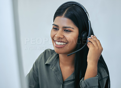 Buy stock photo Shot of an attractive young saleswoman sitting alone in her office and wearing a headset while using her computer