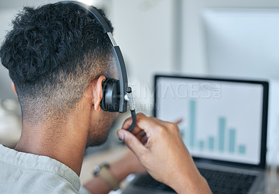 Buy stock photo Shot of an unrecognizable salesman sitting alone in his office and wearing a headset while using his laptop