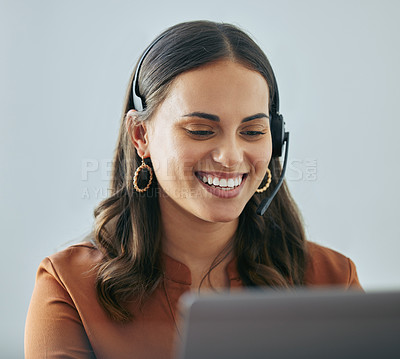 Buy stock photo Shot of an attractive young saleswoman sitting alone in her office and wearing a headset while using her laptop