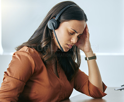 Buy stock photo Shot of an attractive young saleswoman sitting alone in her office and suffering from a headache