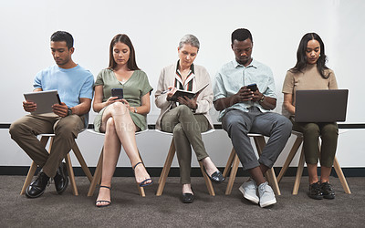 Buy stock photo Shot of a group of businesspeople using digital devices while sitting together in a line against a white wall