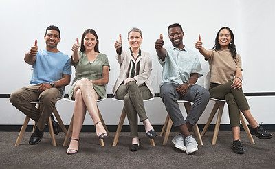 Buy stock photo Portrait of a group of businesspeople showing thumbs up while sitting together in a line against a white wall