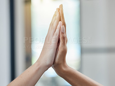 Buy stock photo Closeup shot of two unrecognisable businesspeople giving each other a high five in an office