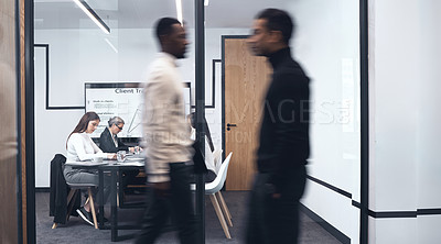 Buy stock photo Shot of two work colleagues walking by one another at the office