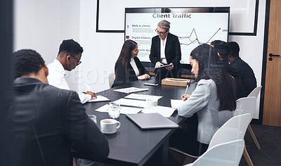 Buy stock photo Shot of a mature businesswoman giving a presentation to her staff while using a digital tablet