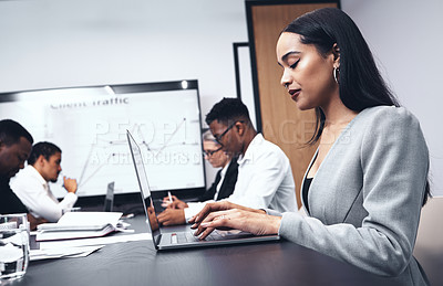 Buy stock photo Shot of a young businesswoman using her laptop in the office