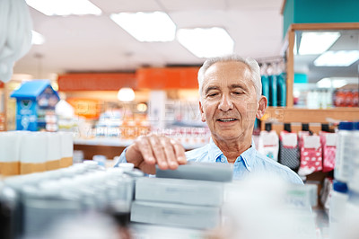 Buy stock photo Cropped shot of a handsome senior man shopping for medication in a pharmacy