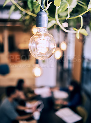 Buy stock photo Shot of a lightbulb hanging in a cafe