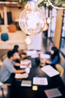 Buy stock photo Shot of a lightbulb hanging over a group of creatives working together
