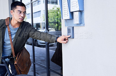 Buy stock photo Shot of a young man pressing a button outside of a building