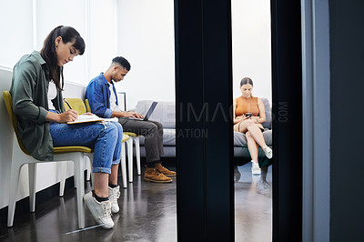 Buy stock photo Shot of ta group of people using their devices while waiting to be interviewed in a modern office