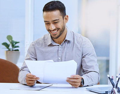 Buy stock photo Shot of a businessman looking at paperwork while sitting at his desk