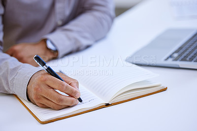 Buy stock photo Cropped shot of an unrecognizable man making notes while sitting at his desk