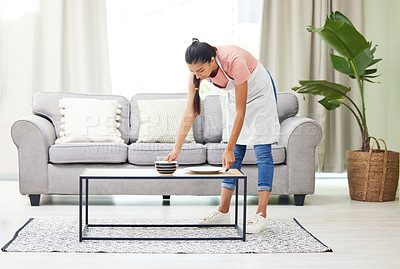 Buy stock photo Shot of a young woman removing dirty dishes from a coffee table in the living room at home