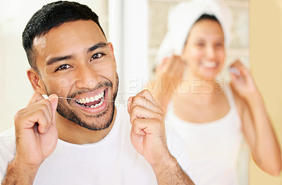 Buy stock photo Shot of a happy young couple flossing their teeth in the bathroom at home