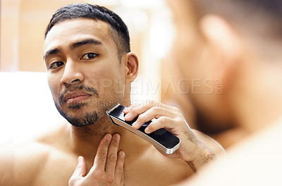 Buy stock photo Shot of a young man using an electric shaver