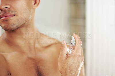 Buy stock photo Cropped shot of a spraying himself with perfume at home