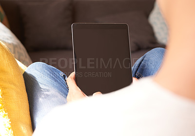 Buy stock photo Cropped shot of an unrecognizable man sitting in his living room and using a digital tablet to work from home