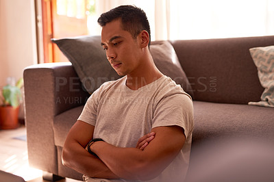 Buy stock photo Shot of a handsome young man sitting alone in his living room and looking contemplative while working from home