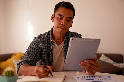 Buy stock photo Shot of a handsome young man sitting alone and using a digital tablet to work from home
