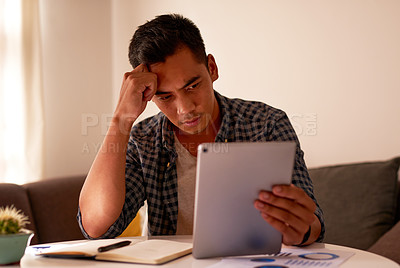 Buy stock photo Shot of a handsome young man sitting alone and feeling stressed while using a digital tablet to work from home