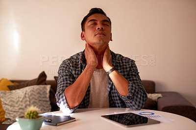 Buy stock photo Shot of a handsome young man sitting alone at home and suffering from a sore neck