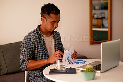 Buy stock photo Shot of a handsome young man sitting alone at home and going through paperwork while working from home