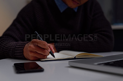 Buy stock photo Cropped shot of an unrecognizable man making notes while working late at home