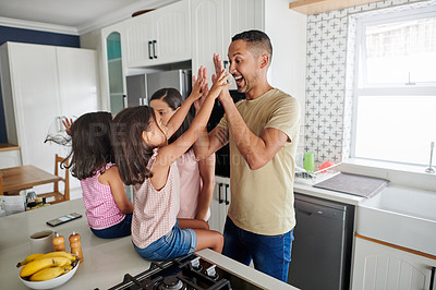Buy stock photo Shot of two adorable little girls playing with their parent's in the kitchen at home