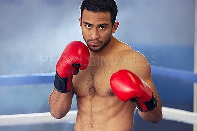 Buy stock photo Cropped portrait of a handsome young male boxer standing with his guard up during a fight in the ring