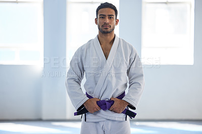 Buy stock photo Cropped portrait of a handsome young male martial artist standing with his hands on his belt in the gym