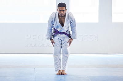 Buy stock photo Full length portrait of a handsome young male martial artist bowing in the gym