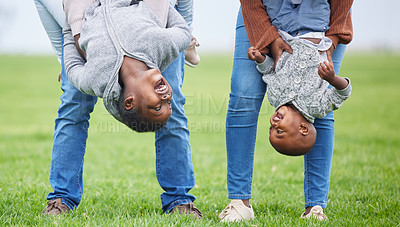 Buy stock photo Shot of two children hanging upside down by their parents outside
