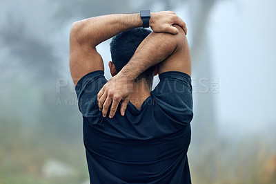 Buy stock photo Rearview shot of a sporty young man stretching his arms while exercising outdoors