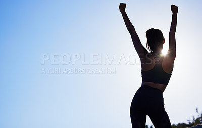 Buy stock photo Rearview shot of a sporty young woman standing with her arms outstretched while exercising outdoors