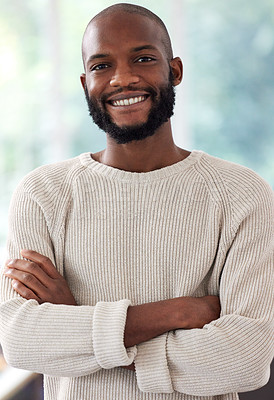Buy stock photo Shot of a young man standing with his arms crossed at home