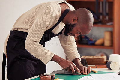 Buy stock photo Cropped shot of a handsome young male designer working with leather in his design studio