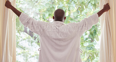 Buy stock photo Shot of a young man opening curtains at home