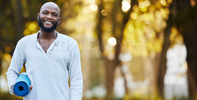 Buy stock photo Cropped portrait of a handsome young man holding his yoga mat while standing outside in the park