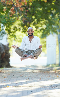 Buy stock photo Full length shot of a handsome young man levitating while meditating outside at the park