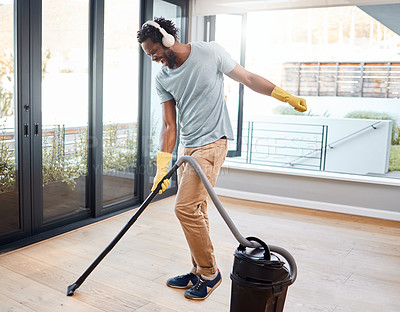 Buy stock photo Shot of a young man wearing headphones while vacuuming at home