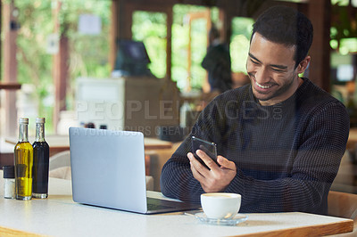 Buy stock photo Shot of a man using his cellphone while sitting with his laptop in a cafe