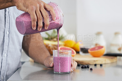 Buy stock photo Cropped shot of a man pouring a freshly blended smoothie into his glass at home