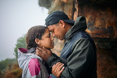 Buy stock photo Shot of a young couple wearing their rain jackets while out hiking