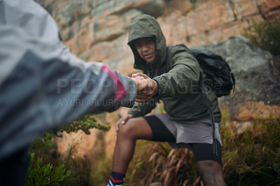 Buy stock photo Shot of a man helping his partner up a cliff while mountain climbing
