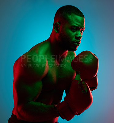 Buy stock photo Studio shot of a sporty young man wearing boxing gloves