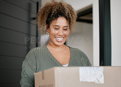 Buy stock photo Shot of a young woman carrying a box at home