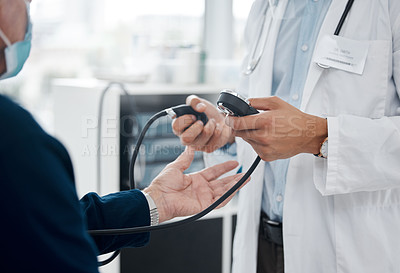 Buy stock photo Shot of an unrecognizable doctor checking a patient's blood pressure in an office