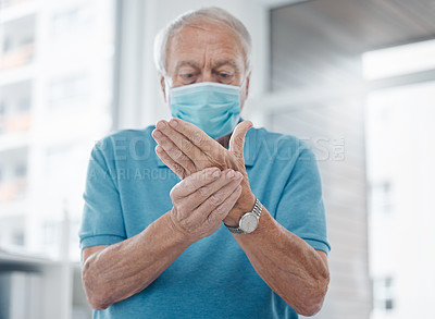 Buy stock photo Shot of a mature man feeling his hands in a hospital