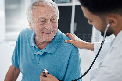 Buy stock photo Shot of a young doctor examining a mature man with a stethoscope in an office